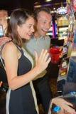 Ζεύγος που διεγείρεται με το αποτέλεσμα μηχανημάτων τυχερών παιχνιδιών με κέρματα Στοκ φωτογραφίες με δικαίωμα ελεύθερης χρήσης