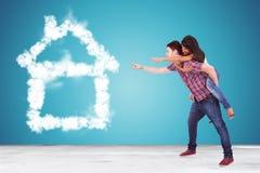 Ζεύγος που δείχνει το σπίτι ονείρου τους φιαγμένο από σύννεφα Στοκ Εικόνες