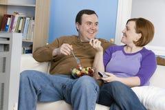 Ζεύγος που εξετάζει μεταξύ τους τρώγοντας τα φρούτα Στοκ Φωτογραφία