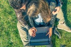 Ζεύγος που εξετάζει τον υπολογιστή σε ένα πάρκο Στοκ φωτογραφία με δικαίωμα ελεύθερης χρήσης