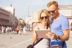 Ζεύγος που εξετάζει τον υπολογιστή ταμπλετών διακινούμενο στη Βενετία Στοκ εικόνες με δικαίωμα ελεύθερης χρήσης