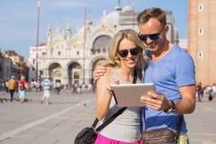 Ζεύγος που εξετάζει τον υπολογιστή ταμπλετών διακινούμενο στη Βενετία Στοκ Εικόνες