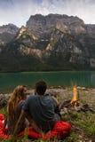 Ζεύγος που εξετάζει το ένα το άλλο και που χαλαρώνει στο μέτωπο μιας όμορφης λίμνης από την Ελβετία με την πυρκαγιά εκτός από Στοκ εικόνες με δικαίωμα ελεύθερης χρήσης