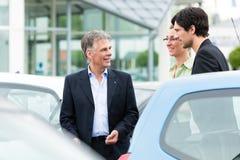 Ζεύγος που εξετάζει το αυτοκίνητο στην αυλή του εμπόρου Στοκ Εικόνες