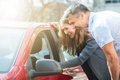 Ζεύγος που εξετάζει το αυτοκίνητο στοκ εικόνα με δικαίωμα ελεύθερης χρήσης