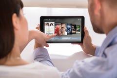 Ζεύγος που επιλέγει τους σε απευθείας σύνδεση κινηματογράφους στην ψηφιακή ταμπλέτα στοκ εικόνες