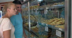 Ζεύγος που επιλέγει τα νόστιμα μπισκότα στο παντοπωλείο απόθεμα βίντεο