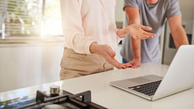 Ζεύγος που εργάζεται μαζί σε ένα lap-top στην κουζίνα Στοκ Εικόνες