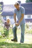 Ζεύγος που εργάζεται στον κήπο στο σπίτι από κοινού Στοκ Εικόνες