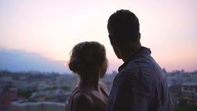Ζεύγος που θαυμάζει το όμορφο ρόδινο ηλιοβασίλεμα που τυλίγει ήπια τους, άποψη από τη στέγη απόθεμα βίντεο