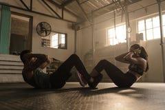 Ζεύγος που κάνει το κάθομαι-UPS μαζί στη γυμναστική στοκ φωτογραφίες με δικαίωμα ελεύθερης χρήσης