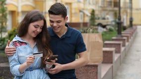 Ζεύγος που καθιστά την αγορά σε απευθείας σύνδεση με το τηλέφωνο υπαίθρια απόθεμα βίντεο