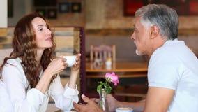 Ζεύγος που κουβεντιάζει και καφές κατανάλωσης απόθεμα βίντεο