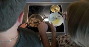 Ζεύγος που μαγειρεύει μαζί το κρέας και τη σάλτσα απόθεμα βίντεο