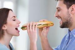 Ζεύγος που μοιράζεται το σάντουιτς στοκ φωτογραφίες