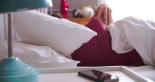 Ζεύγος που ξυπνιέται από το συναγερμό στο κινητό τηλέφωνο αργά για την εργασία απόθεμα βίντεο