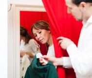 Ζεύγος που δοκιμάζει το παλτό στο συναρμολόγηση-δωμάτιο στοκ εικόνες