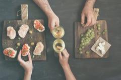 Ζεύγος που πίνει το άσπρο κρασί με τα πρόχειρα φαγητά για το κρασί Στοκ Εικόνα