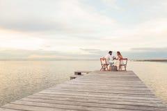 Ζεύγος που πίνει το κόκκινο κρασί στην παραλία σε έναν λιμενοβραχίονα Στοκ εικόνες με δικαίωμα ελεύθερης χρήσης