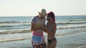 Ζεύγος που παίρνει ένα selfie και που έχει τη διασκέδαση στην ακτή μιας αμμώδους παραλίας απόθεμα βίντεο