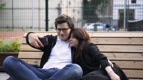 Ζεύγος που παίρνει ένα selfie σε ένα έδρανο κοντά σε ένα γήπεδο αντισφαίρισης απόθεμα βίντεο