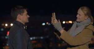 Ζεύγος που παίρνει τις φωτογραφίες της πόλης νύχτας με το PC ταμπλετών απόθεμα βίντεο