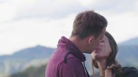 Ζεύγος που περπατά ενάντια στο σκηνικό των βουνών honeymoon φιλί στο υπόβαθρο των βουνών ο αέρας αναπτύσσεται φιλμ μικρού μήκους