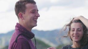 Ζεύγος που περπατά ενάντια στο σκηνικό των βουνών honeymoon φιλί στο υπόβαθρο των βουνών ο αέρας αναπτύσσεται απόθεμα βίντεο