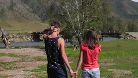Ζεύγος που περπατά ενάντια στο σκηνικό των βουνών honeymoon χέρια και περίπατος λαβής ανδρών και γυναικών στη φύση Ζεύγος μέσα φιλμ μικρού μήκους