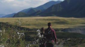 Ζεύγος που περπατά ενάντια στο σκηνικό των βουνών honeymoon χέρια και περίπατος λαβής ανδρών και γυναικών στη φύση Ζεύγος μέσα απόθεμα βίντεο