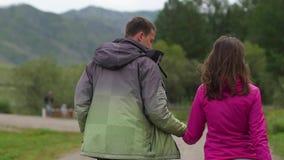 Ζεύγος που περπατά ενάντια στο σκηνικό των βουνών honeymoon χέρια και περίπατος λαβής ανδρών και γυναικών στη φύση o απόθεμα βίντεο
