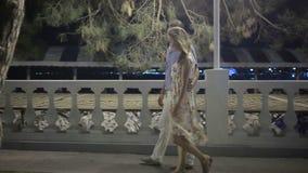 Ζεύγος που περπατά κατά μήκος της οδού στη νύχτα έξω καλός ρομαντικός ζευγών απόθεμα βίντεο