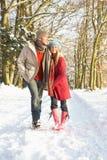Ζεύγος που περπατά μέσω της χιονώδους δασώδους περιοχής στοκ φωτογραφία με δικαίωμα ελεύθερης χρήσης