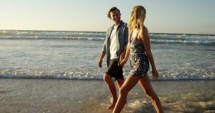 Ζεύγος που περπατά μαζί στην ακτή στην παραλία φιλμ μικρού μήκους