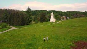 Ζεύγος που περπατά προς τη μικρή άσπρη εκκλησία απόθεμα βίντεο