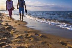 Ζεύγος που περπατά στην παραλία στο φως ηλιοβασιλέματος, Γντανσκ, Πολωνία, έννοια χαλάρωσης Στοκ Εικόνα