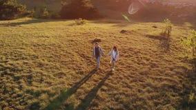 Ζεύγος που περπατά στη φύση στο ηλιοβασίλεμα φιλμ μικρού μήκους