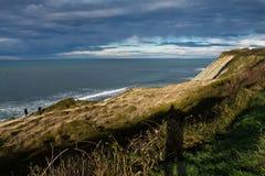 Ζεύγος που περπατά στον ατλαντικό απότομο βράχο προεξοχών ακτών από τον ωκεανό στο θαυμάσιο φως του ήλιου ουρανού στη βασκική χώρ Στοκ εικόνα με δικαίωμα ελεύθερης χρήσης