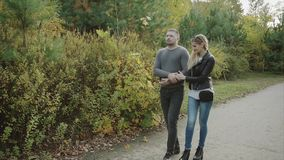 Ζεύγος που περπατά στο πάρκο φθινοπώρου φιλμ μικρού μήκους
