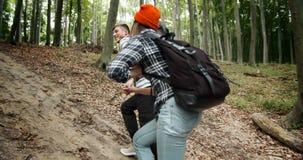 Ζεύγος που πηγαίνει ανηφορικά στο δάσος απόθεμα βίντεο