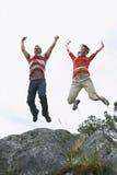 Ζεύγος που πηδά με τα όπλα που αυξάνονται πέρα από το βράχο Στοκ εικόνα με δικαίωμα ελεύθερης χρήσης
