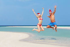 Ζεύγος που πηδά στην παραλία που φορά τα καπέλα Santa Στοκ Εικόνες