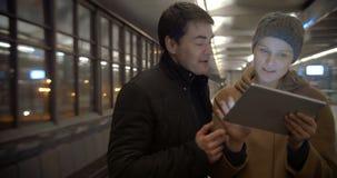 Ζεύγος που προγραμματίζει το βράδυ τους με το PC ταμπλετών απόθεμα βίντεο