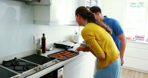 Ζεύγος που προετοιμάζει τα μπισκότα στην κουζίνα απόθεμα βίντεο