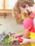 Ζεύγος που πλένει τα φρέσκα λαχανικά στην κουζίνα Στοκ Εικόνες