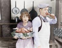 Ζεύγος που στέκεται μαζί σε μια κουζίνα με μια μαγειρευμένη Τουρκία (όλα τα πρόσωπα που απεικονίζονται δεν ζουν περισσότερο και κ Στοκ εικόνες με δικαίωμα ελεύθερης χρήσης