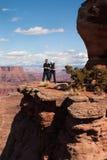 Ζεύγος που στέκεται σε μια άκρη ενός φαραγγιού, πάρκο Canyonlands Natioanal Στοκ Φωτογραφία