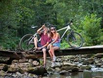 Ζεύγος που στηρίζεται στο δάσος στη γέφυρα κοντά στα ποδήλατα Στοκ εικόνες με δικαίωμα ελεύθερης χρήσης