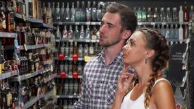 Ζεύγος που συζητά το κρασί για την πώληση στην υπεραγορά απόθεμα βίντεο