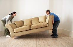 Ζεύγος που τοποθετεί τον καναπέ στο καθιστικό του νέου σπιτιού Στοκ Φωτογραφία